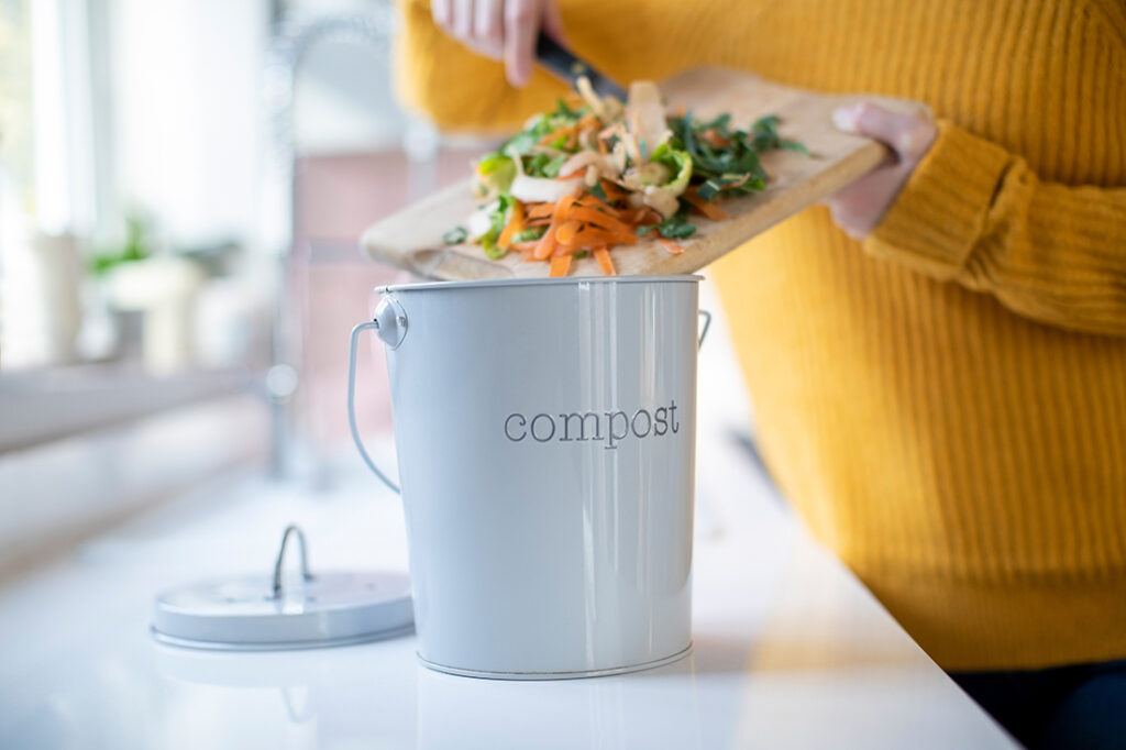 Close Up Of Woman Making Compost From Vegetable Leftovers In Kitchen